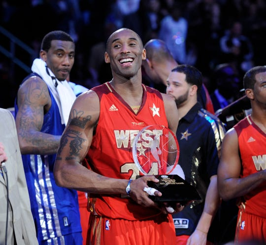 Kobe Bryant celebrates being awarded the MVP trophy during the 2011 NBA All-Star Game at Staples Center in Los Angeles.